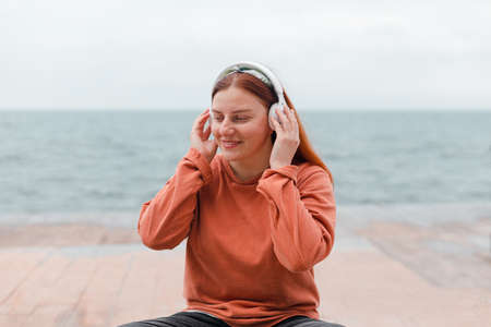 Close up portrait of young smile girl meditates with wireless headphones outdoors on beach Banque d'images