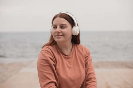 Close up portrait of young girl meditates with wireless headphones outdoors on beach against the sea