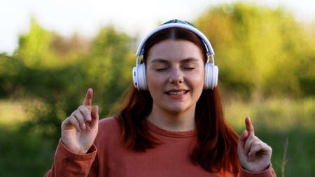 Woman with eyes closed listening music through headphone