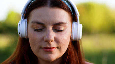 Beautiful caucasian woman with closed eyes listening to music using wireless headphones and smartphone in city park Banque d'images