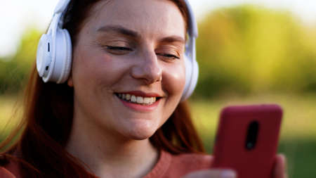 Attractive happy young girl student listening to music with headphones. Student using mobile phone chatting.