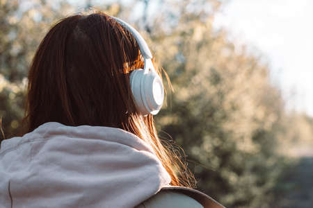 Back view of caucasian young woman listening music with headphones on a sunny day while walking in city park Banque d'images