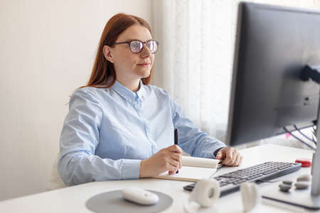 Close up portrait of beautiful caucasian american woman smiling and looking at a computer screen in office or remote work Banque d'images