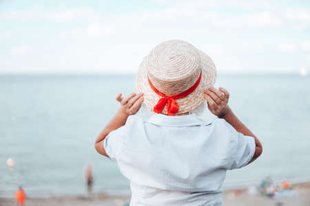 Back view of attractive young woman in straw hat at the seaside during summer vacation. Happy girl with blond hair enjoying a sun. Panoramic horizontal summer sale banner Banque d'images