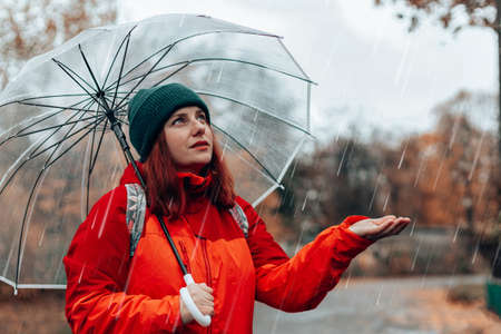 Caucasian woman with backpack and in red jacket walks along wet rainy streets under a transparent umbrella