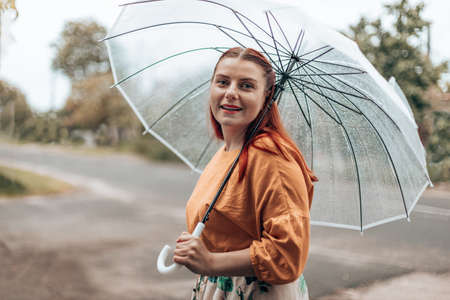 Beautiful contented female in bright clothes under a transparent umbrella in bad weather.