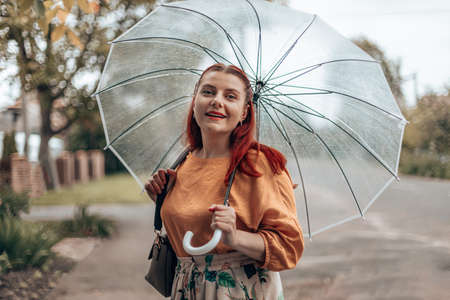 Stylish young woman in bright clothes under a transparent umbrella in bad weather. Banque d'images