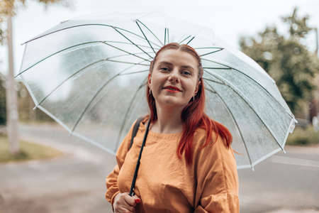 Happy young woman in bright clothes under a transparent umbrella in bad weather in the city park