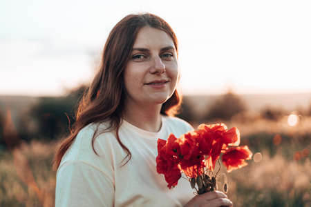 Woman hand holding red poppies bouquet at sunset in the field