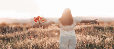 Caucasian Happy beautiful young girl with a poppy bouquet in her hands in a summer field at sunset. Tourism, traveling and healthy lifestyle concept.