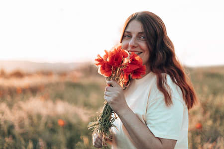 Happy young girl with a poppy bouquet in her hands in a summer field at sunset. Woman looking at the camera Banque d'images