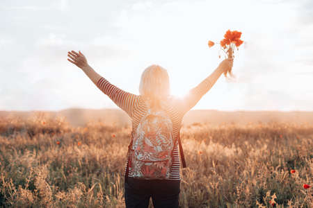 Adult woman tourist with backpack and poppy flower bouquet at sunset in the field. summer vacation. Happy girl with blond hair enjoying the sun. Horizontal banner