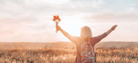 Back view of Caucasian woman tourist with backpack and poppy flower bouquet at sunset in the field. Tourism, traveling and healthy lifestyle concept.