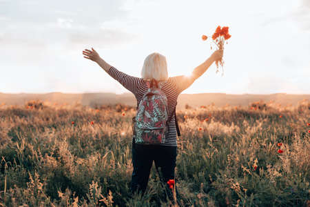 Back view of woman tourist with backpack and poppy flower bouquet at sunset in the field. Summer vacation. Happy girl enjoying the sun. Horizontal banner Banque d'images