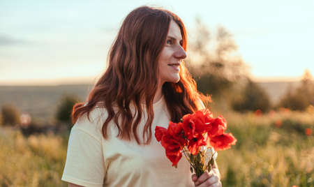 Beutiful young red-haired woman hand holding red poppies bouquet in the field at sunset