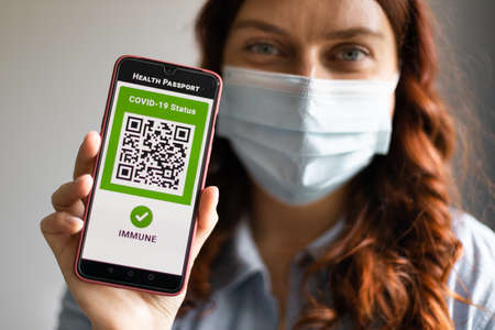 Young girl wearing a face mask holding a passport, ticket pass and smartphone with digital health passport app for travel during covid-19 pandemic.