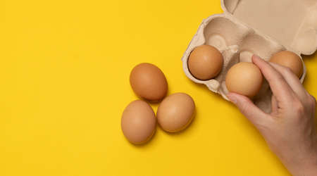 Easter brown chicken eggs in eco basket and one egg on yellow background. Fresh egg on morning breakfast, flat lay, copy space.