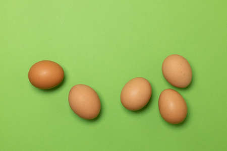Easter brown chicken eggs on a green background