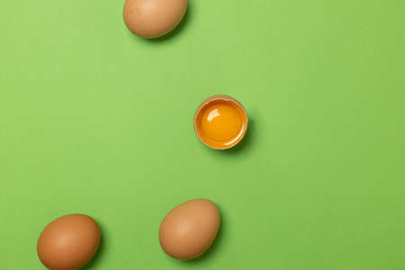 Tasty brown chicken eggs and one broken egg with yolk on green background