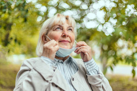 Happy woman takes off her protective medical mask from her face enjoying nature and fresh air after the end of the pandemic