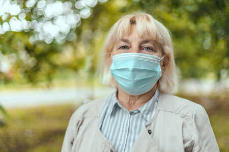 Close up portrait caucasian businesswoman is looking at camera while wearing a protective mask