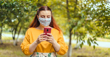 Happy woman walking using mobile phone wearing face mask protection as prevention for virus in city park Banque d'images