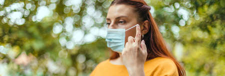 Relaxed happy girl takes off her protective medical mask from her face to breathe fresh air after the end of the pandemic. No more quarantine