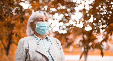 woman in medical face protection mask outdoors in autumn park Banque d'images