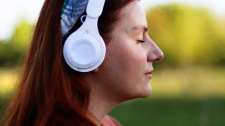 Side view of caucasian young woman listening music with headphones on a sunny day while walking in city park