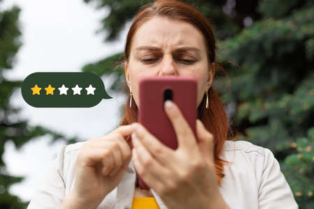 Close up on woman hand press on smartphone screen with gold two star rating feedback icon