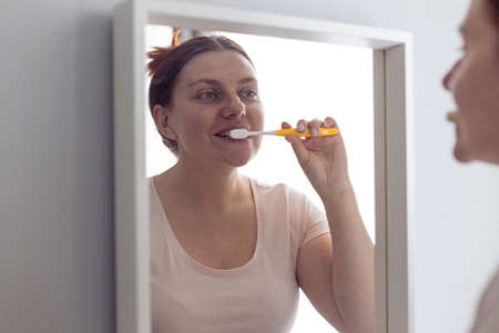 Portrait of beautiful millennial woman brushing teeth looking in mirror during morning hygiene procedures in the bathroom. Hygiene, dental care concept.
