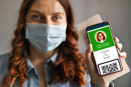 Smartphone screen with digital health passport app. Vaccinated person using health passport app in mobile phone for travel during pandemic. Banque d'images
