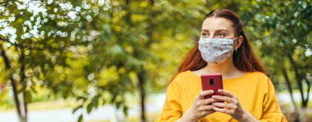 Young woman wearing medical mask using smart phone app in city park