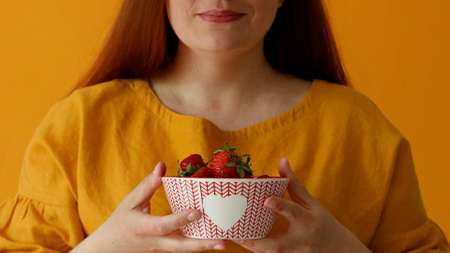 Young woman holding in hands and gives fresh large juicy strawberries. Healthy food Banque d'images