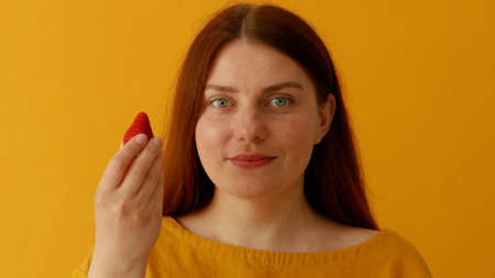 Delicious strawberry dessert. Portrait of woman smiles in good mood as eats favorite dessert holds red berry. Banque d'images