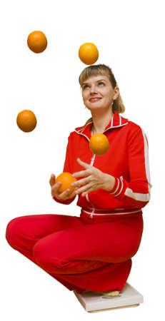 La imagen de la ni�a se sent� en el suelo y las escalas de malabares con naranjas Foto de archivo - 3926013