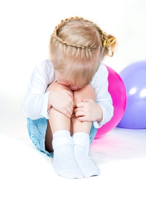 The little girl sits having embraced knees