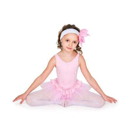 Full-length portrait of a little girls practicing her ballet kicks on a white background