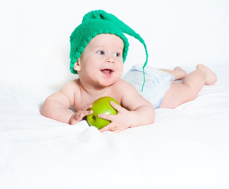 The kid in a green cap with apple Stock Photo - 15530247