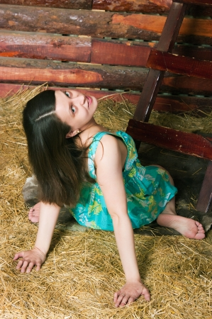 The image of the girl sitting on hay