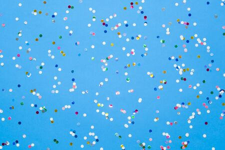 Colored confetti scattered on blue pastel paper