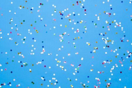 Kolorowe konfetti rozrzucone na niebieskim papierze pastelowym