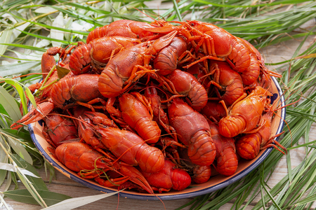 red, boiled, crayfish in a Cup on a rough wooden table