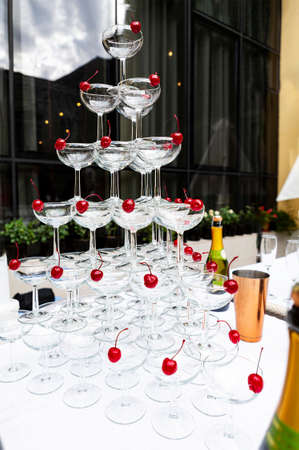Pyramda of champagne glasses at a buffet at a wedding party. Secular reception, new year, wedding. Soft focus. Glasses with Proseko at the holiday. Many glasses of champagne in a luxurious setting