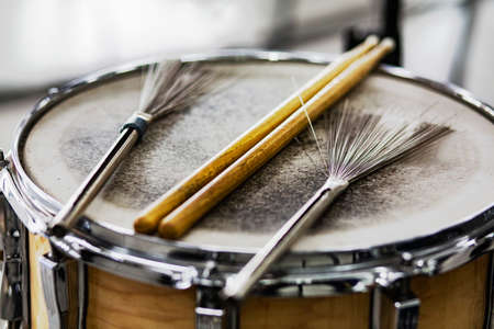 Drum sticks and wire brushes on an old leather drum. Detail of snare drum drum sticks. Percussion musical instruments. Soft focus.