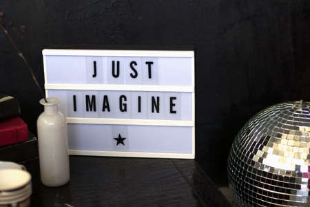 Light led box with typesetters font just imagine stands on a leather table next to a vase, flowers and books. Blur