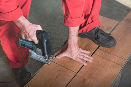 A worker in a red jumpsuit cuts a laminate with a jigsaw by marking, resting his foot on the bar. Master saws the bar with an electric saw in the workshop. Carpenter