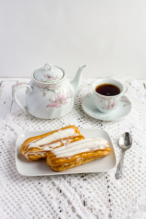 puff: Dessert Eclair with whipped cream and sugar icing on a white table Stock Photo
