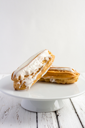 Dessert Eclair with whipped cream and sugar icing on a white table Stock Photo