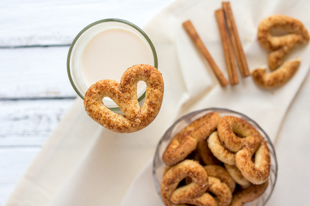 pretzel: Pretzel with cinnamon and sugar on a white table and a glass of milk